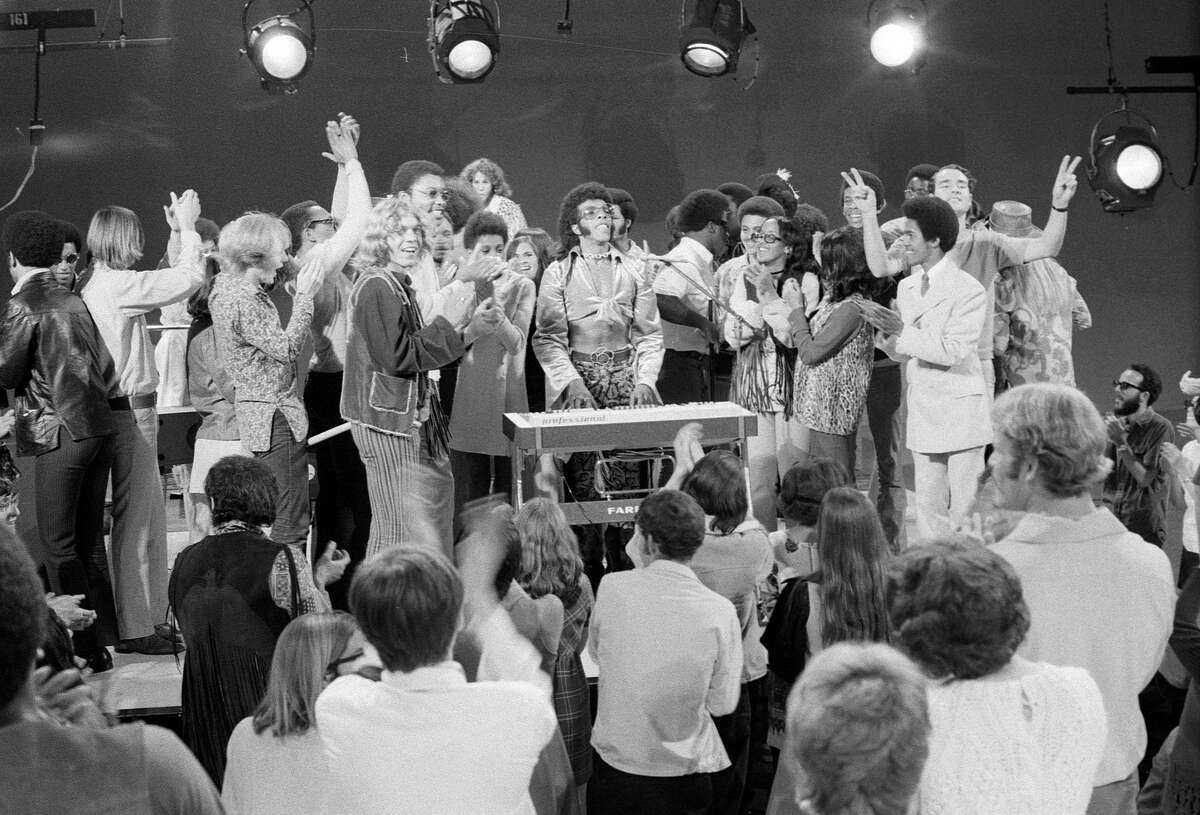 The audience joined Sly and the Family Stone on stage on television on October 15, 1969. Sly Stone is in the center with glasses.