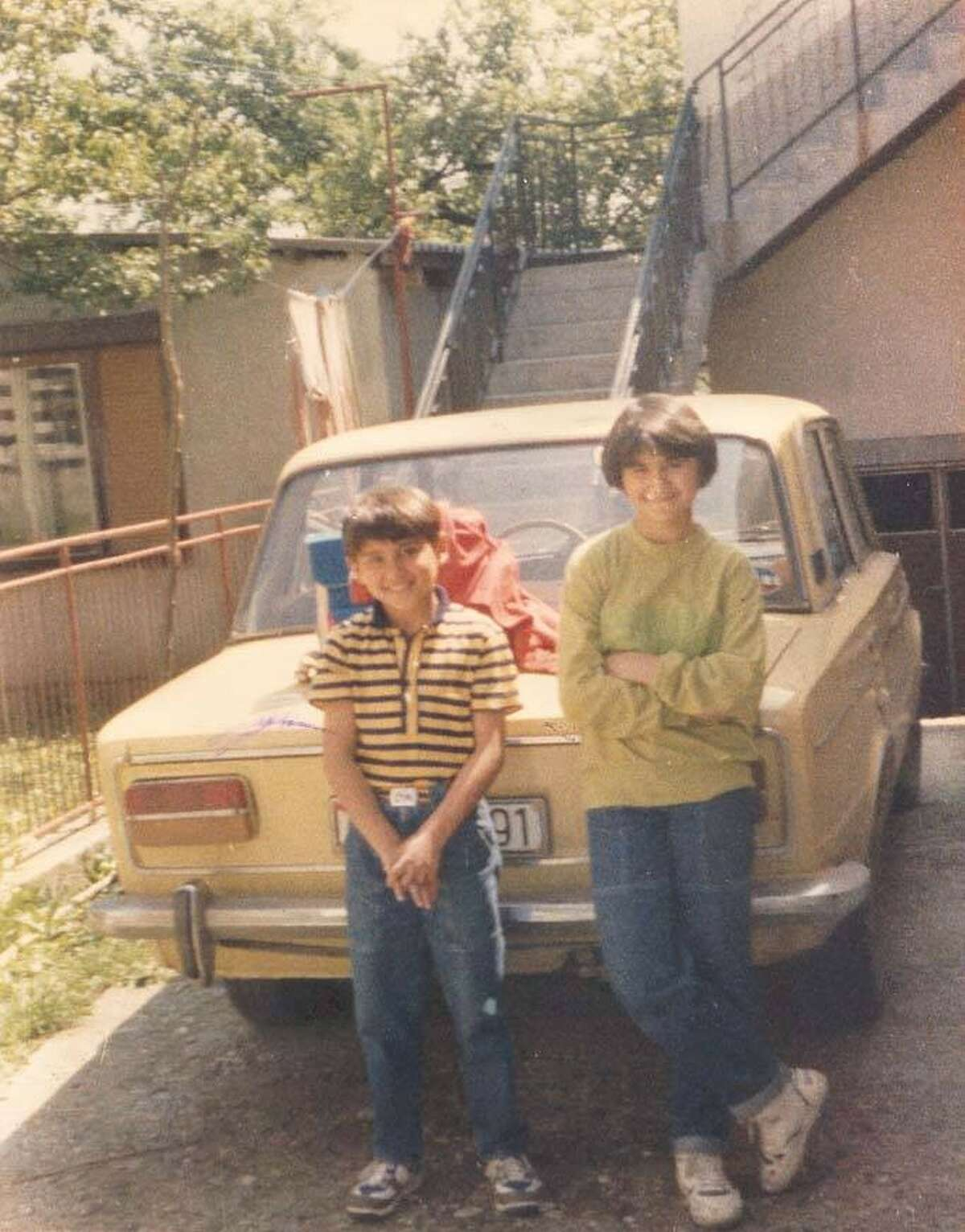 Aimal Kanic, age 13, with her little brother stike a pose next to their dad's beloved yellow Lada. They lived happily in what is now Bosnia until war broke out. They fled the morning after Serbian soldiers began going door to door arresting all Muslim men and boys. The horrible reason for the roundup would soon be clear.