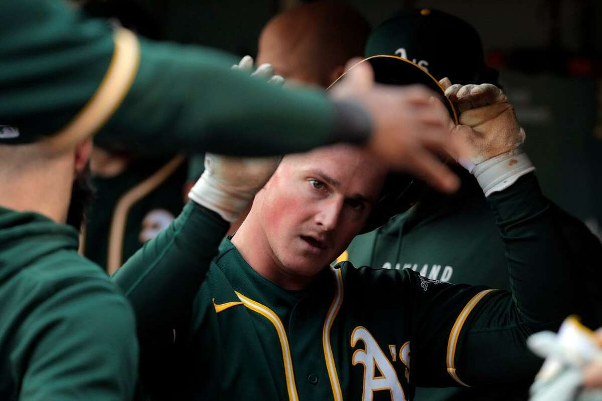 Matt Chapman (26) gets high fives from teammates iafter scoring in the second inning as the Oakland Athletics played the Texas Rangers at the Coliseum in Oakland, Calif., on Wednesday, June 30, 2021.