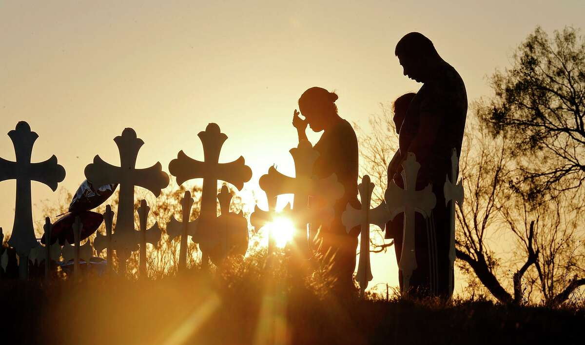 Irene (left) and Kenneth Hernandez (right) with their daughter Miranda pray the day after the shooting at First Baptist Church of Sutherland Springs in 2017 before 26 crosses set up for those killed.
