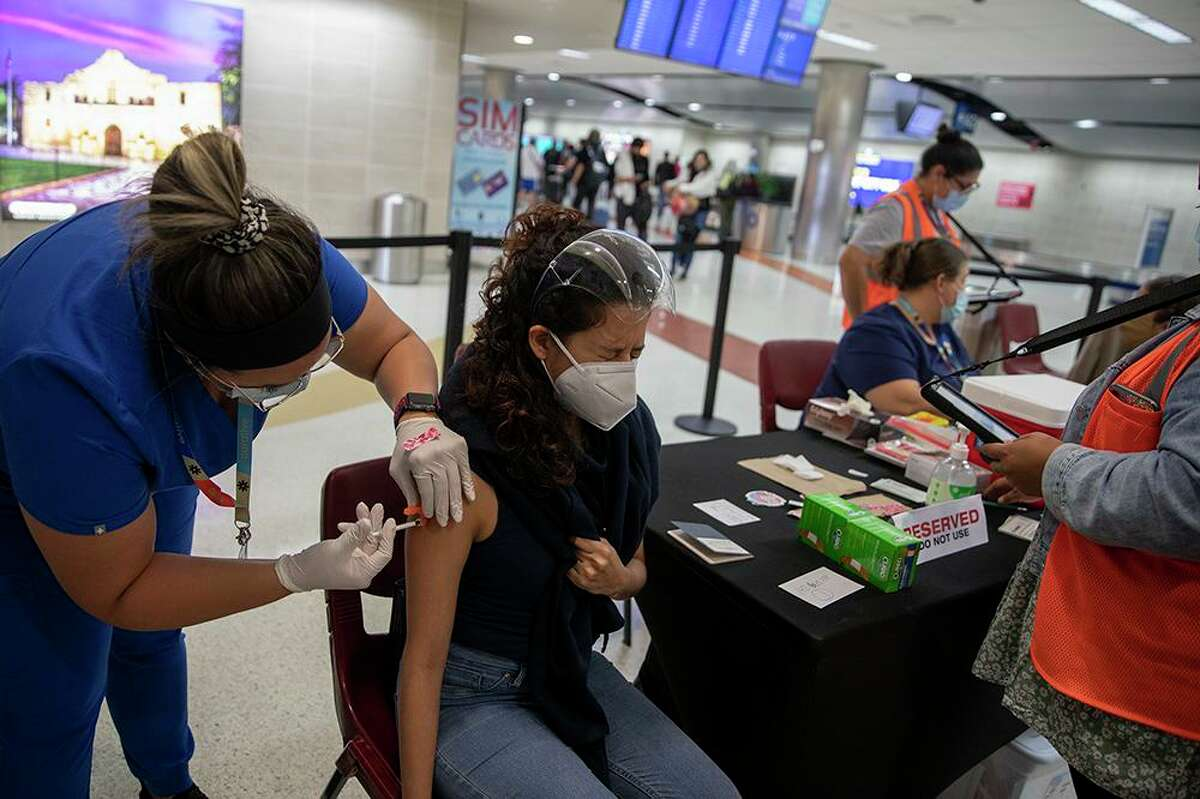 Katias Flores receives her COVID vaccine at the San Antonio International Airport after traveling from Mexico City with her father.