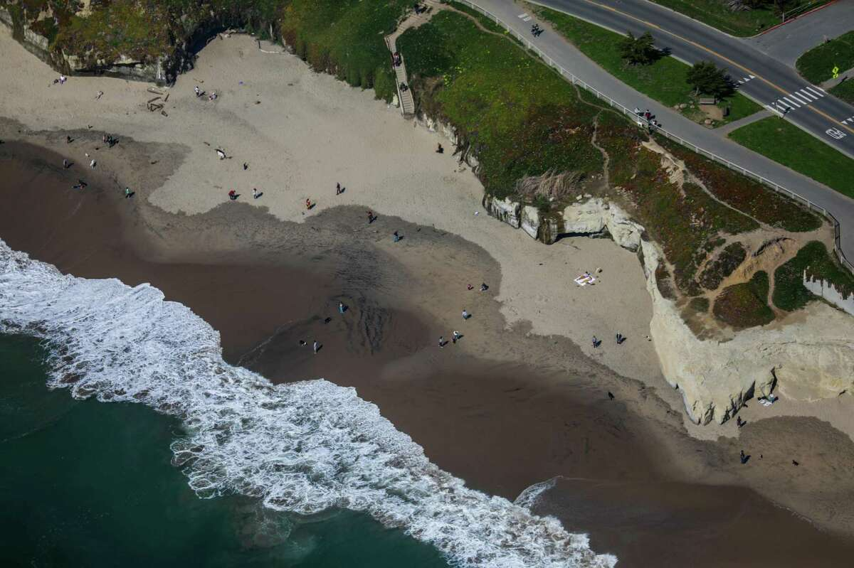 A view of the people along the coastline between Watsonville and Half Moon Bay during a helicopter flight which was chartered to search for the remains of 12-year-old boy Arunay Pruthi who was pulled into the ocean over Martin Luther King weekend at Cowell Ranch State Beach on Monday, March 1, 2021 near Half Moon Bay, California.