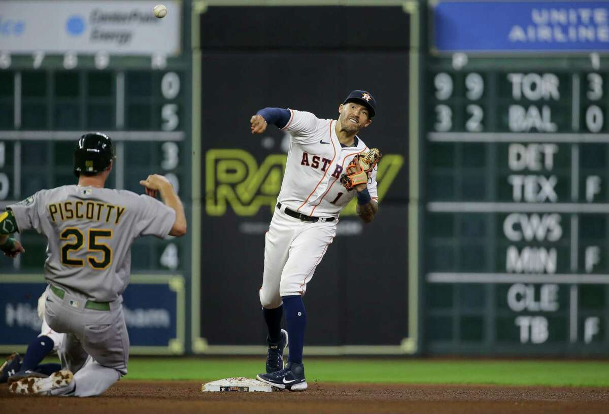 Houston Astros shortstop Carlos Correa (1) tries to turn a double lay against the Oakland Athletics during the fifth inning of an MLB game at Minute Maid Park on Wednesday, July 7, 2021, in Houston.
