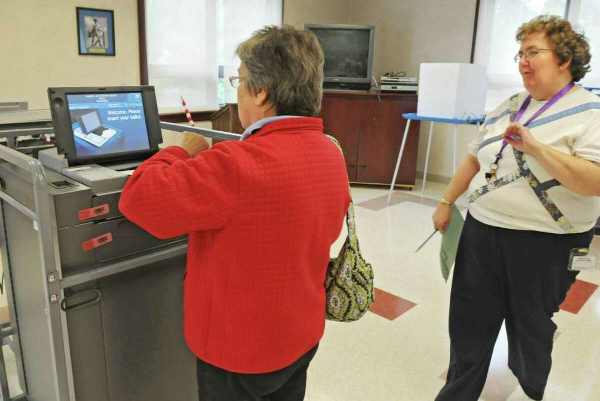 Janet Rausch, left, of Guilderland, gets some pointers from poll worker Debbie Tanski as she places her ballot in the new voting machine at the Western Turnpike Rescue Squad polling place in Guilderland on September 14, 2010. (Lori Van Buren / Times Union)