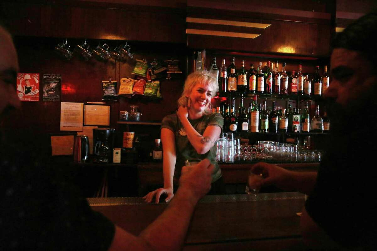 Roxzann De Marco (center), owner of The Rumpus Room, watches as regulars Chris Harrison (right) of San Francisco and Peter Smith (left) of San Francisco share a toast as they sit at the bar on its reopening day.