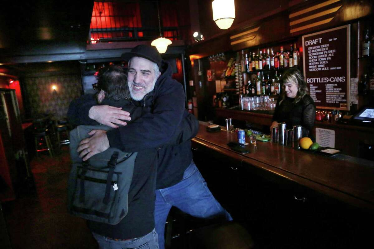 Mike Amaral (right) of Las Vegas and friend Owen Cadigan of Oakland share a welcoming hug at the Rumpus Room reopening in S.F.