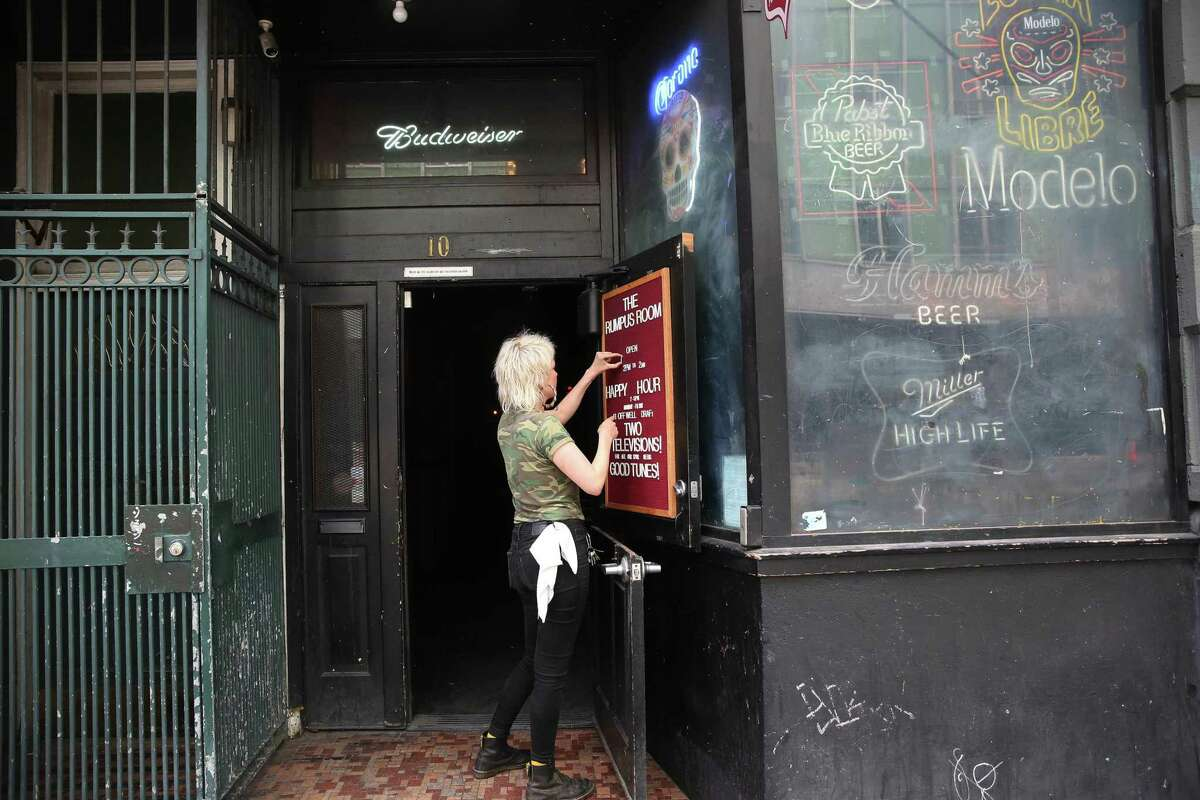 Rumpus Room owner Roxzann De Marco updates the sign at the bar on its reopening day in S.F.