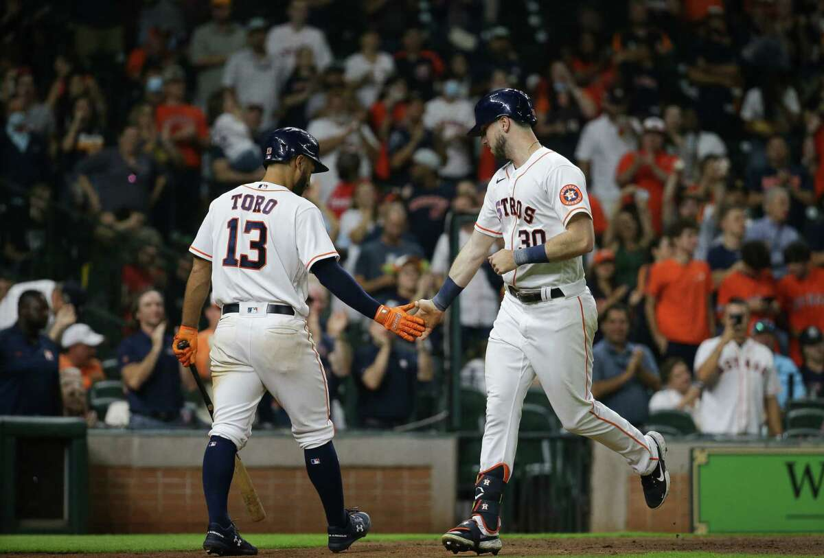 Kyle Tucker (30) celebrates his go-ahead homer in the seventh inning Wednesday with teammate Abraham Toro during the Astros' 4-3 win over the A's at Minute Maid Park.