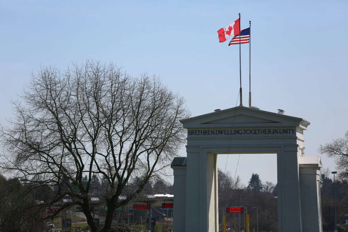 The Canadian and American flags fly above the Peace Arch Border crossing between Canada and the United States, near Seattle, Washington and Vancouver, British Columbia on March 18, 2020.