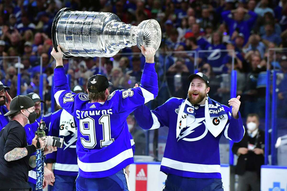 TAMPA, FLORIDA - JULY 07: Steven Stamkos #91 of the Tampa Bay Lightning hands the Stanley Cup to Victor Hedman #77 after the 1-0 victory against the Montreal Canadiens in Game Five to win the 2021 NHL Stanley Cup Final at Amalie Arena on July 07, 2021 in Tampa, Florida.
