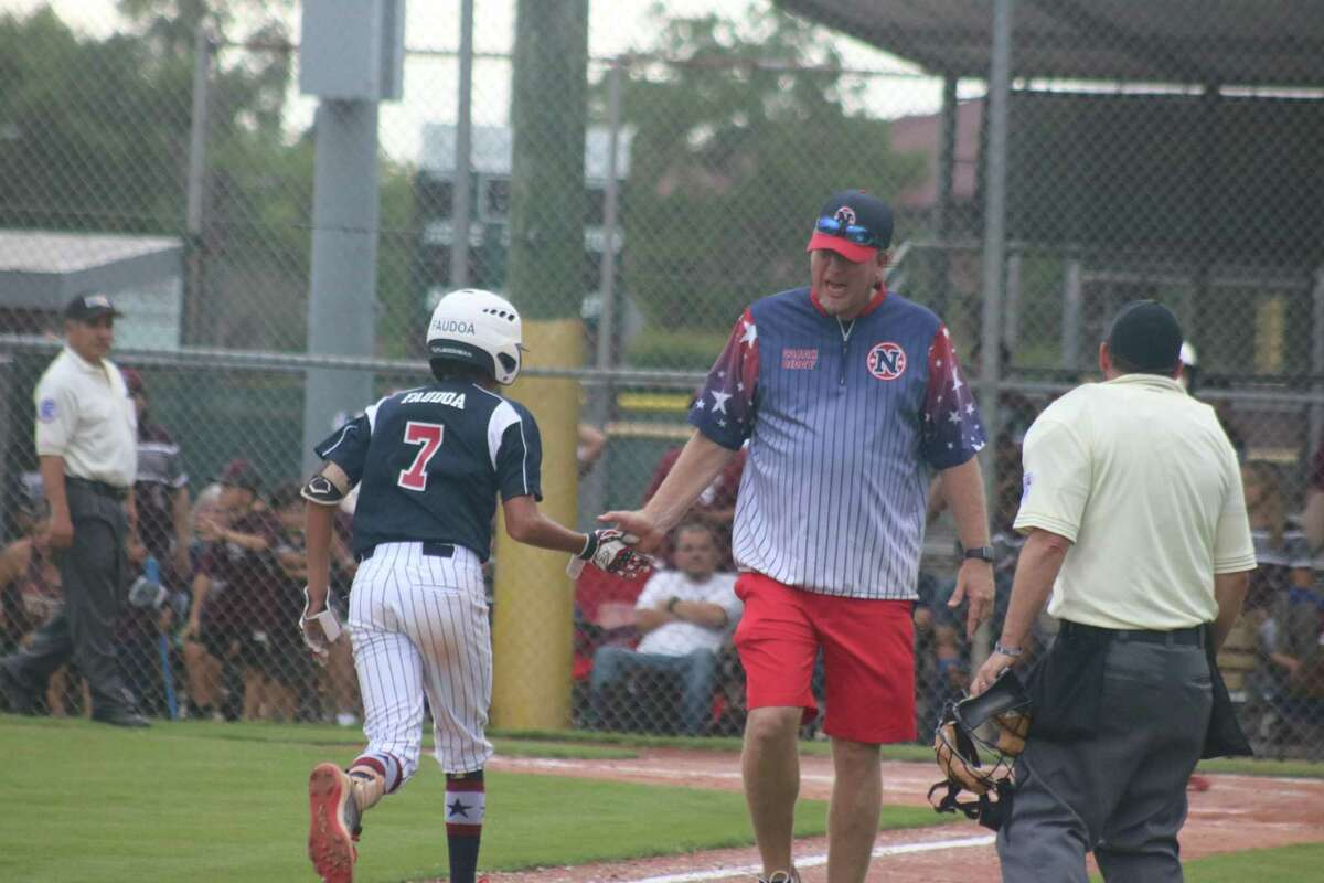NASA 12s manager Jason Biddy congratulates Kaled Faudoa after Faudoa belted a game-tying home run in the fifth inning Wednesday night, a shot that sailed over a 10-foot wall.