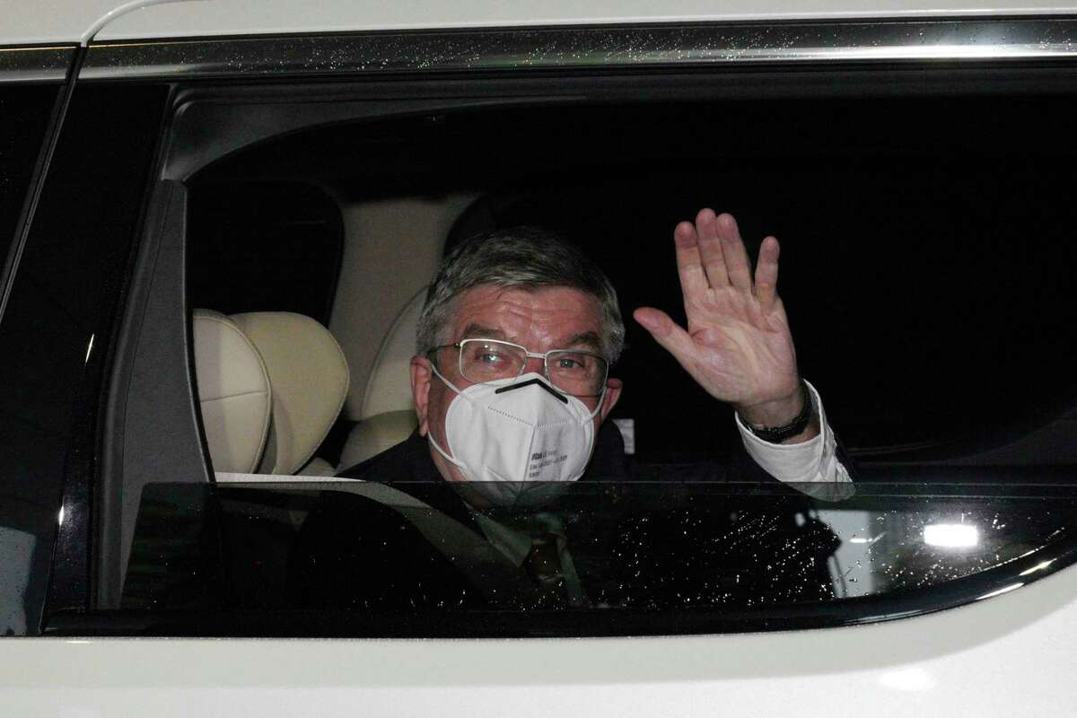 International Olympic Committee (IOC) President Thomas Bach waves from the vehicle to media upon his arrival an accommodation Thursday, July 8, 2021, in Tokyo. Bach arrived on Thursday, July 8, 2021, in Tokyo as Japan Prime Minister Yoshihde Suga was set to declare a state of emergency that is likely to result in a ban on fans from the Tokyo Olympics as coronavirus infections spread across the capital.
