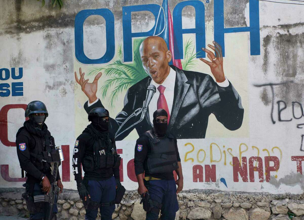 Police stand near a mural featuring Haitian President Jovenel Moise, near the leader's residence where he was killed by gunmen in the early morning hours in Port-au-Prince, Haiti, Wednesday, July 7, 2021.