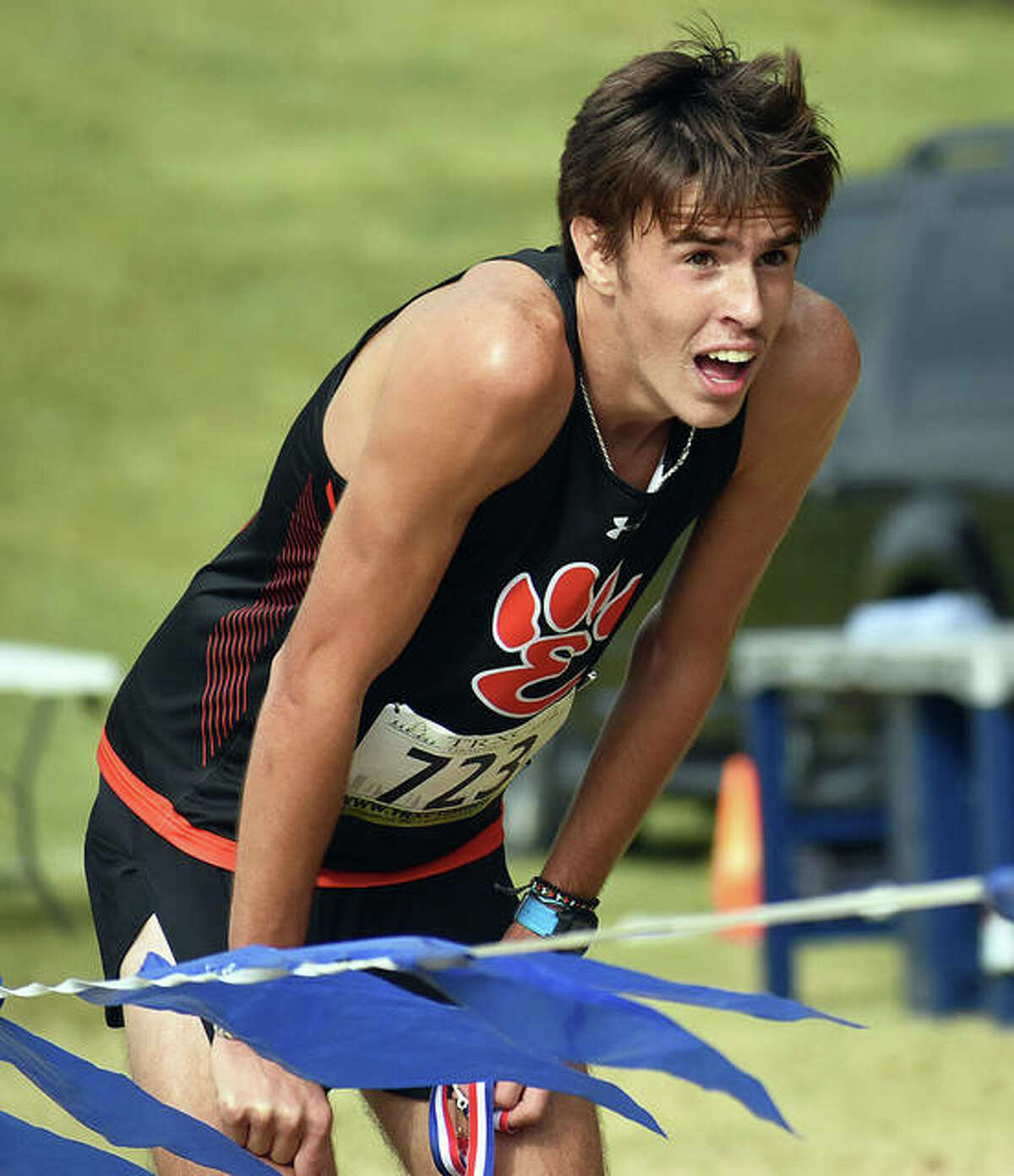 Edwardsville's Ryan Watts watches teammates approach the finish line after his victory in the SWC Meet last season in Swansea.