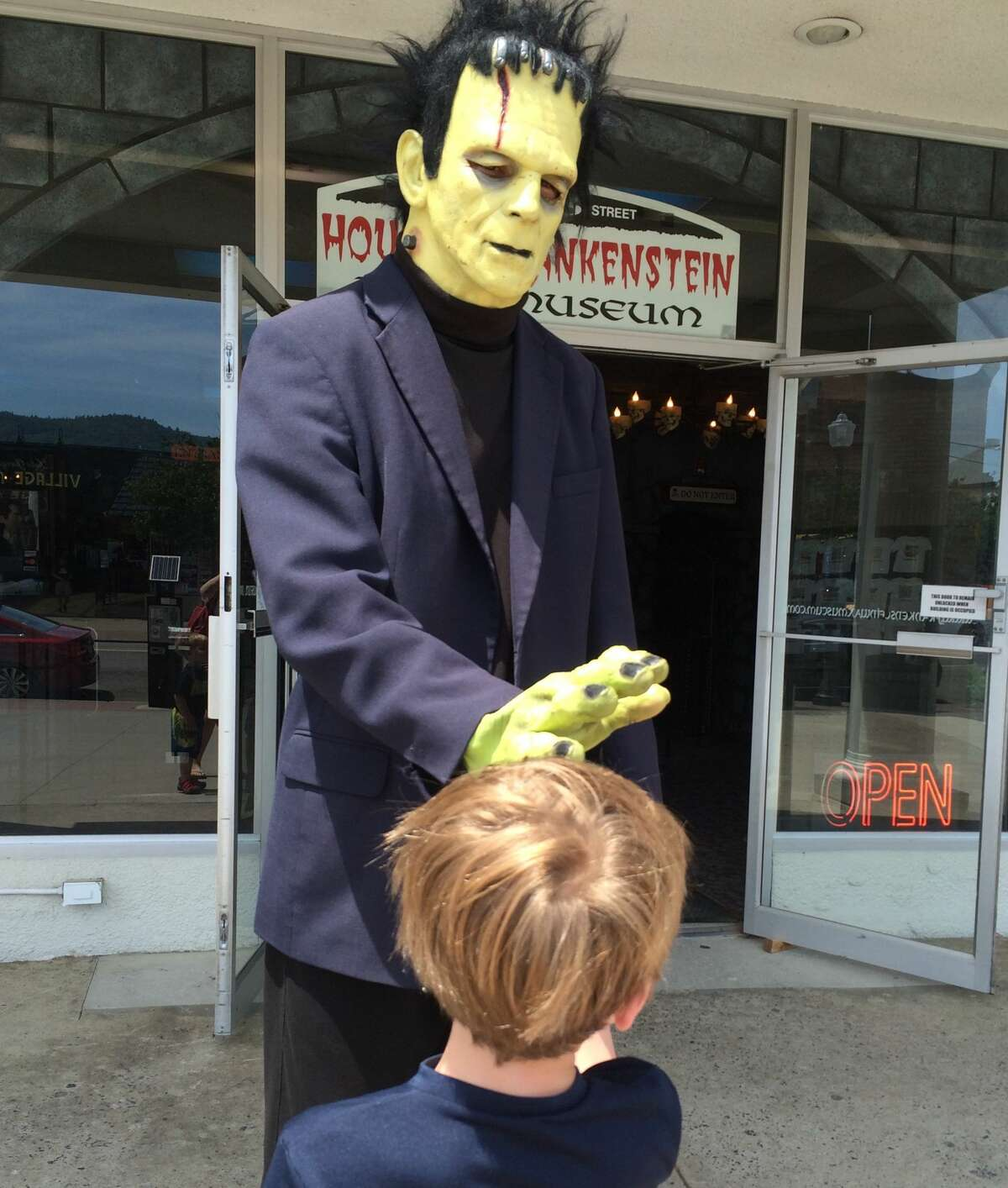 Frankenstein gives a high-five to a boy outside of theHouse of Frankenstein Wax Museum in Lake George. This year's worker shortage means that Frankenstein does not man the door at the Lake George attraction.