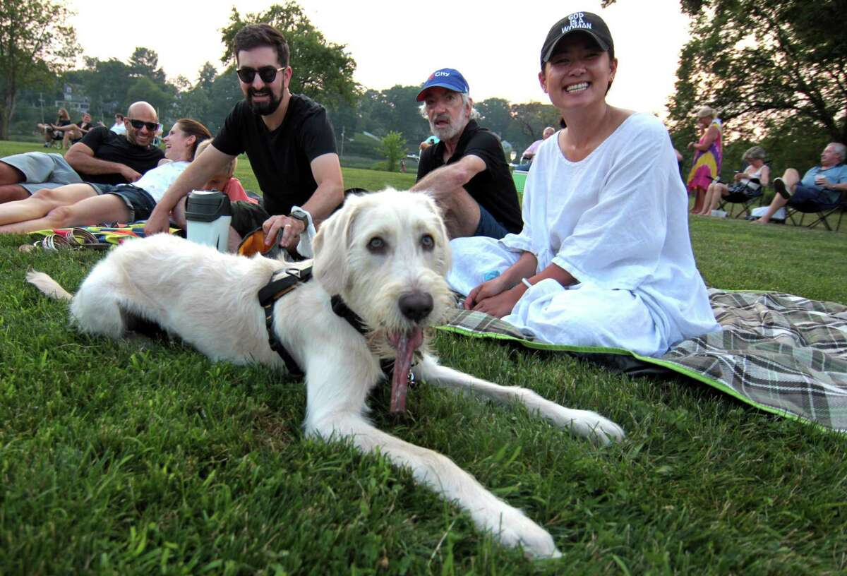 Juno enjoys a treat as Neil Solomon, his dad Ray, center, and Selena Shen enjoy Soul'd Again performing Motown favorites at Roger Sherman Baldwin Park in Greenwich, Conn., on Wednesday July 7, 2021.