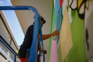 """Donkeeboy working on """"Bike Through H-Town"""" mural, located in downtown's GreenStreet."""