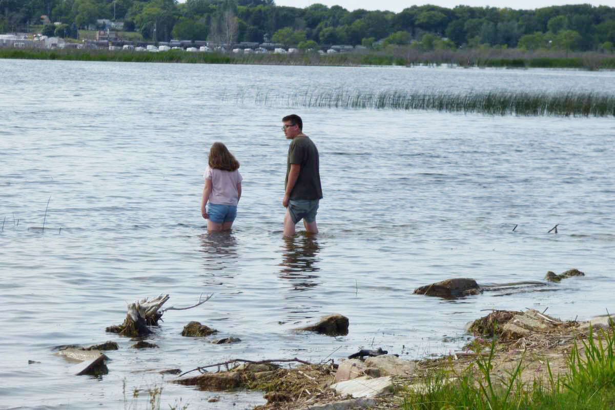 A pair of vacationers wade into Lake Manistee at Eastlake's Penny Park on July 2. Water levels at the lake have caused damage to the park in recent years.