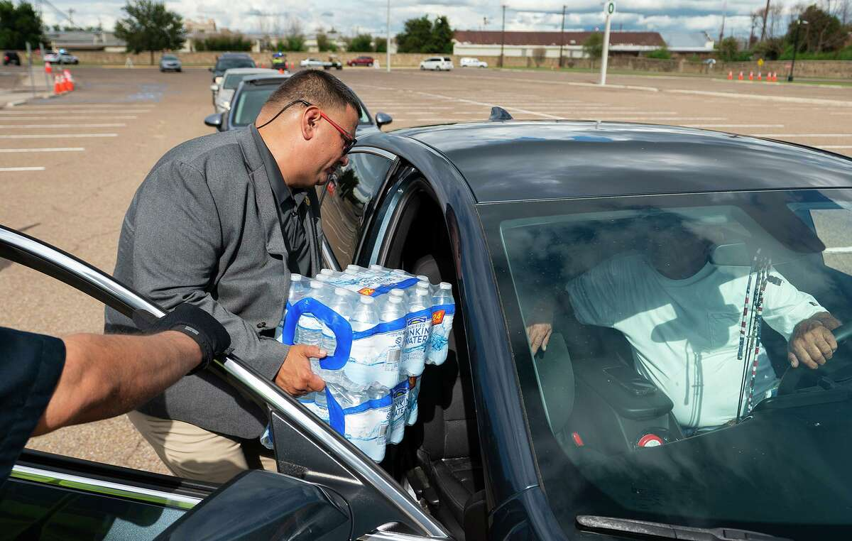 Vice President of Compliance and Risk Management David V. Arreazola, M.S., Ed.D. helps deliver cases of water to vehicles on Thursday, July 7, 2021 at Laredo College during a water distribution in response to a city-wide boil water notice.