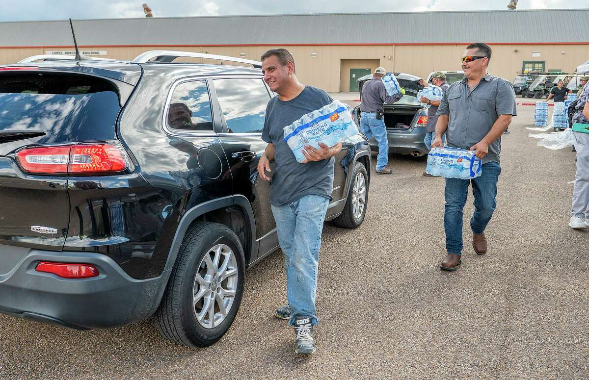 Laredo College employees Daniel Guerrero and Sergio Martinez deliver cases of water to vehicles, Thursday, July 7, 2021, at Laredo College during a water distribution in response to a city wide boil water notice.