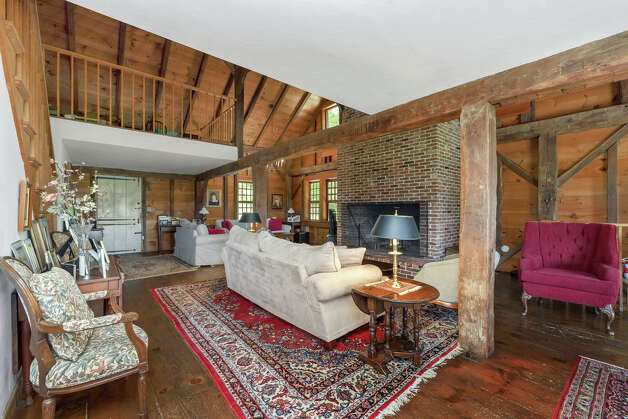 The living room in the Elijah Marshal Barn shows original details such as exposed wood walls and beams. View listing Photo: Noah Butler / Alpha Photography