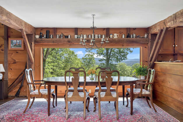 The dining room in theElijah Marshal Barn has a massive picture window overlooking the mountains. View listing Photo: Noah Butler / Alpha Photography