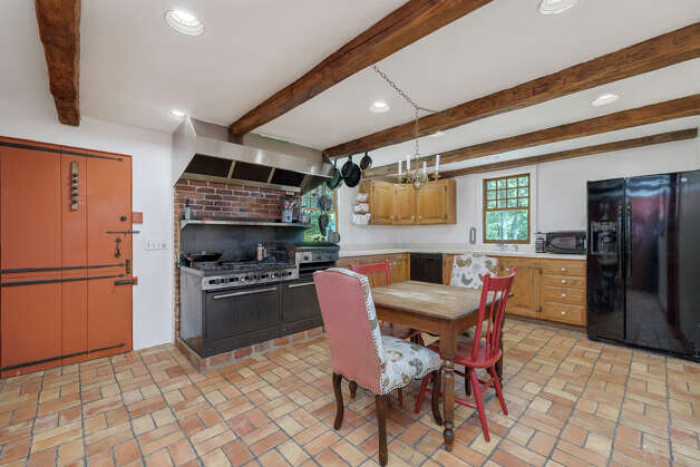 The kitchen in theJosiah Curtis House has exposed wood beams in the ceiling. View listing Photo: Noah Butler / Alpha Photography