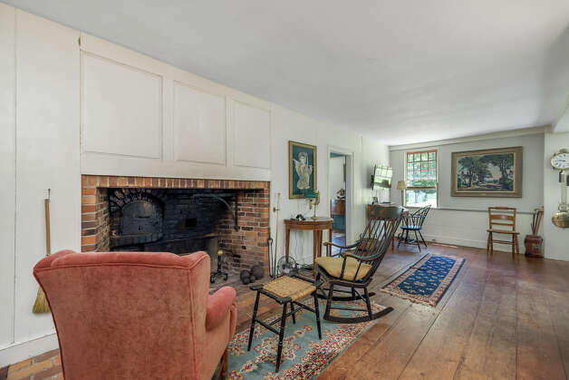 The living room in theJosiah Curtis House has a wood-burning fireplace and wide-plank wood floors. View listing Photo: Noah Butler / Alpha Photography