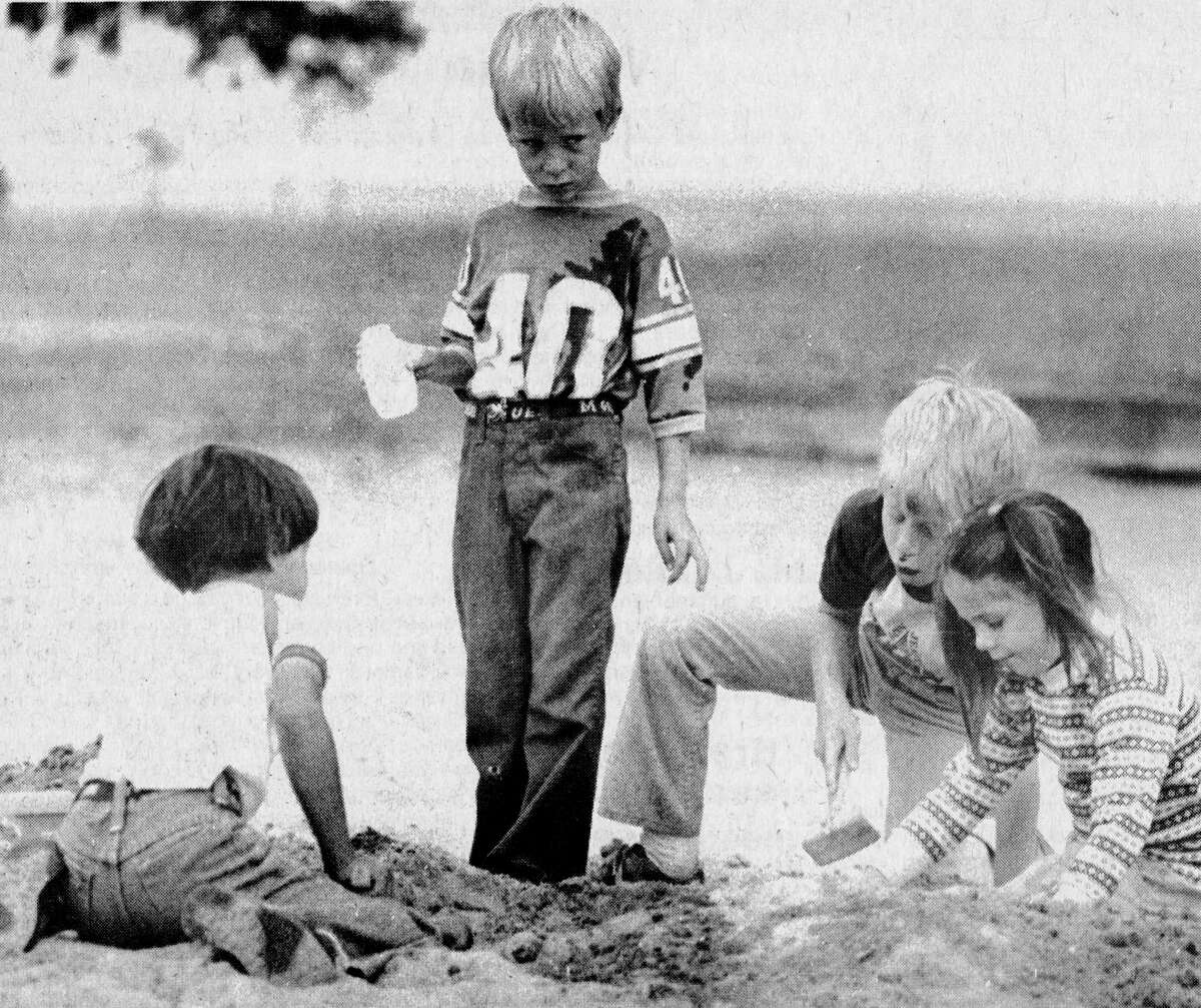 Tommy Morin (left), Becky Morin (right), Joshua Hegg (second right) move sand as Zach Hegg gets ready to pour water to make some mud. The youngsters were building a mud sandcastle at First Street Beach this morning and it could be the start of a new housing district. The photo was published in the News Advocate on July 9, 1981. (Manistee County Historical Museum photo)