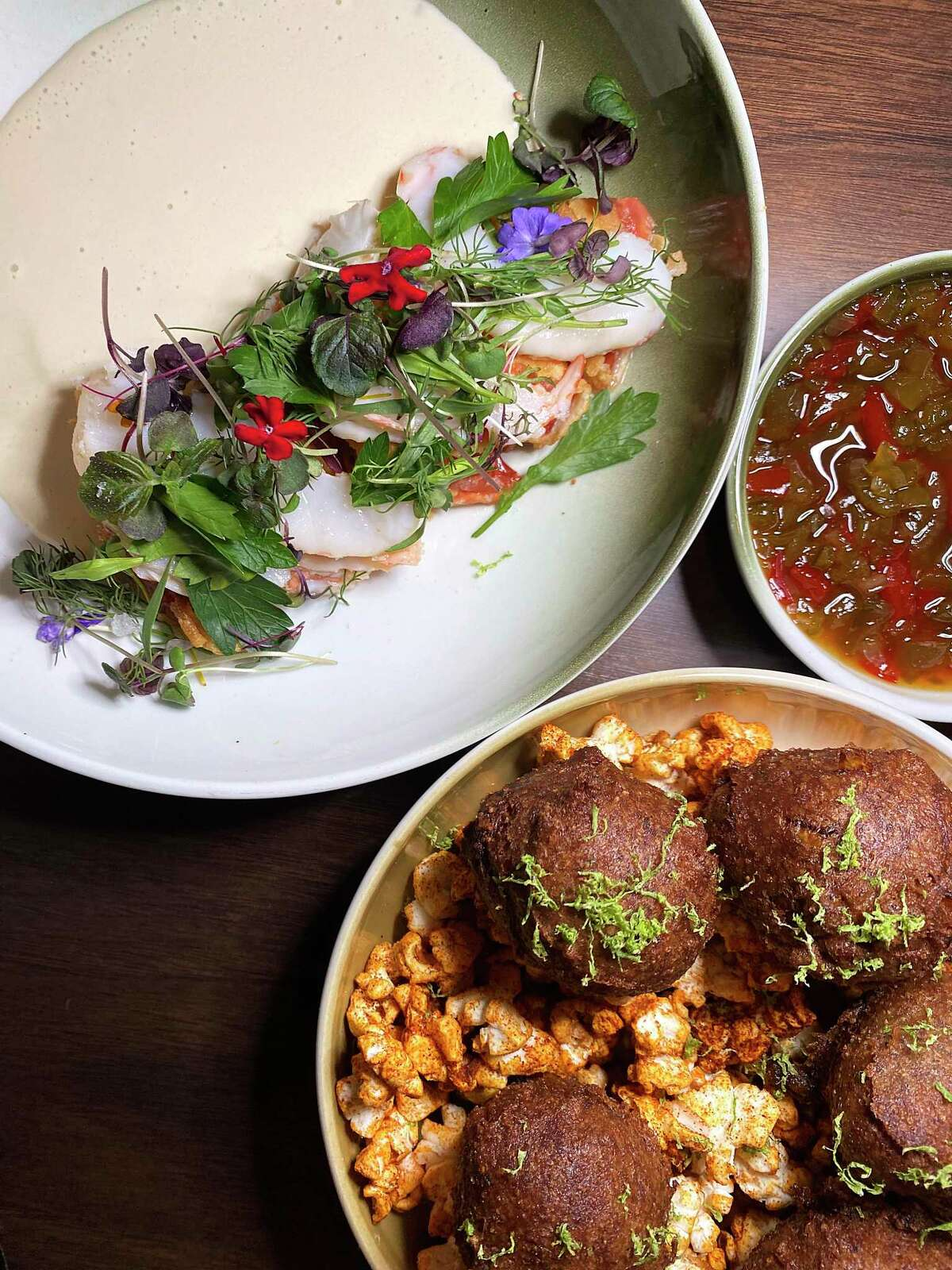 Small plates include tomato schnitzel with pickled shrimp and white gazpacho, top left, and Hopi blue corn hushpuppies with chile lime popcorn and pepper jelly at Landrace.