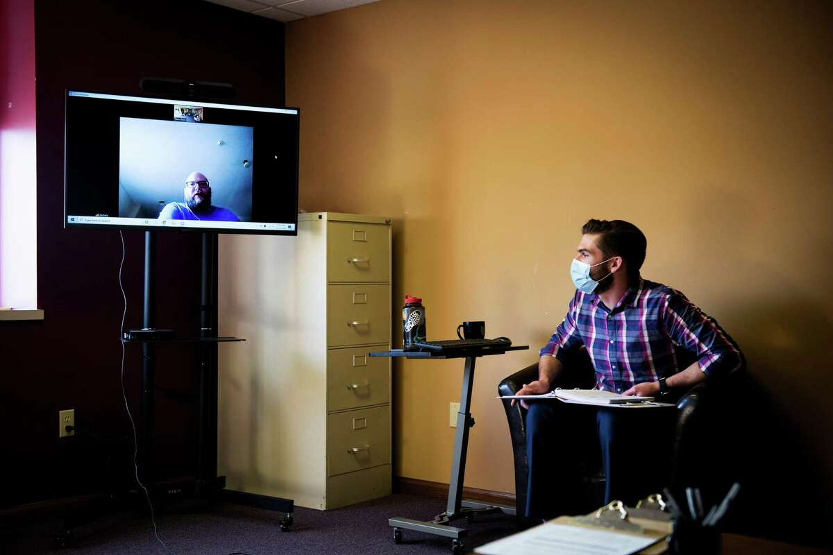 Jason Paris, right, a clinician at Ottagan Addictions Recovery, leads a combination in-person and tele-health intensive outpatient therapy group, in Grand Haven, Mich., on Nov. 20, 2020.