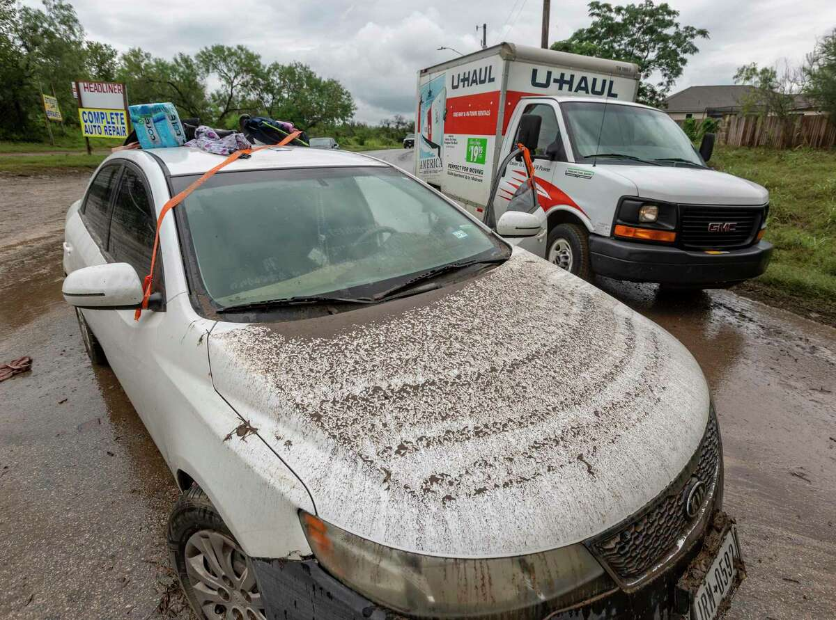 A U-Haul truck passes a flooded car Tuesday in the middle of Heath Road next to Leon Creek after heavy rain caused flooding in the creek that runs through the Northwest and West sides of San Antonio.