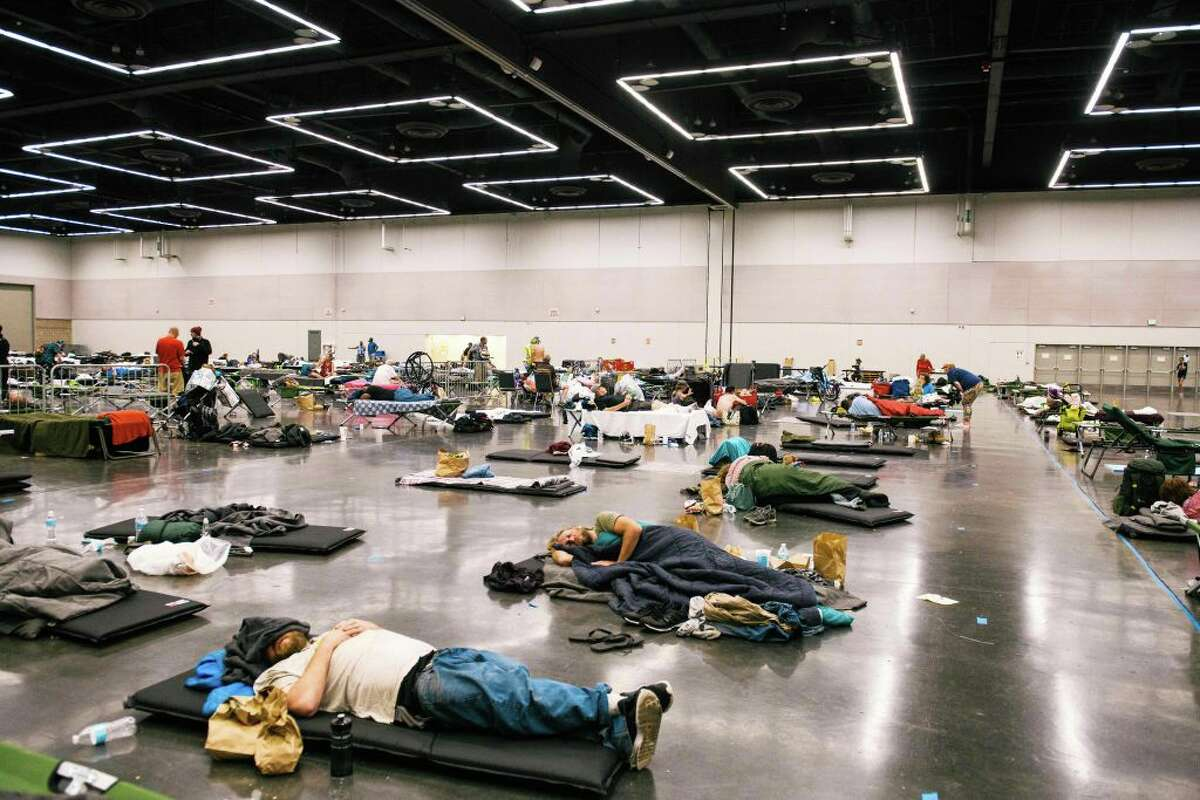 People rest at the Oregon Convention Center cooling station in Oregon, Portland on June 28, 2021, as a heatwave moves over much of the United States. - Swathes of the United States and Canada endured record-setting heat on June 27, 2021, forcing schools and Covid-19 testing centers to close and the postponement of an Olympic athletics qualifying event, with forecasters warning of worse to come. The village of Lytton in British Columbia broke the record for Canada's all-time high, with a temperature of 46.6 degrees Celsius (116 Fahrenheit), said Environment Canada.