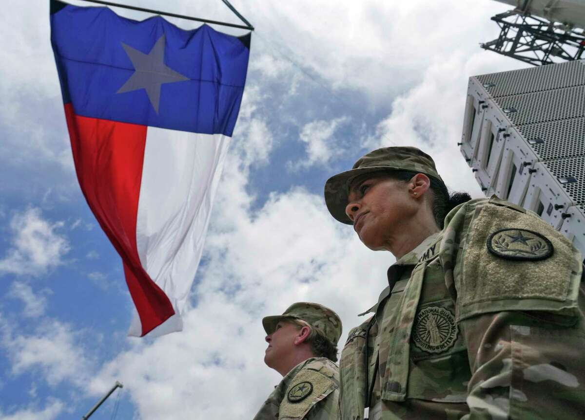 Members of the Army National Guard listen to former President Donald Trump and Texas Gov. Greg Abbott speak near a section of the border wall on June 30 in Pharr.