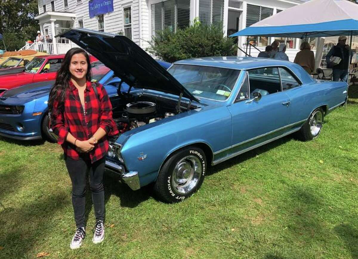 Sarah Leavy stands with a 1967 Chevelle at one of Memory Lane Cruisers' annual car shows. The 20-year-old Ridgefielder grew up attending many of the club's events, and even helped DJ while she was undergoing treatment for HLH, a rare genetic disease.