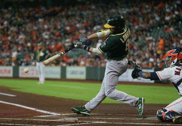 Oakland Athletics designated hitter Jed Lowrie (8) hits an RBI single to center field against the Houston Astros during the first inning of an MLB game at Minute Maid Park on Thursday, July 8, 2021, in Houston. Photo: Godofredo A. Vásquez, Staff Photographer / © 2021 Houston Chronicle