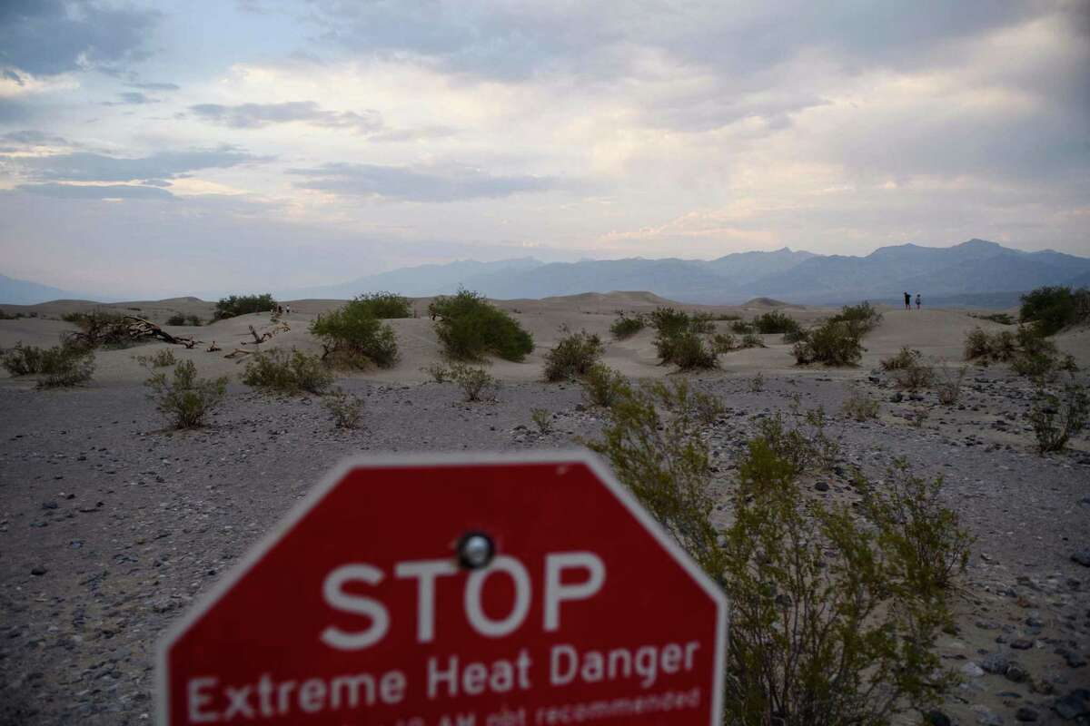 Extreme heat danger signage stands as visitors walk along sand dunes at sunset inside Death Valley National Park in Inyo County, California. The heat wave descending on most of the state has pushed temperatures in Death Valley, just four degrees shy of the world's record.