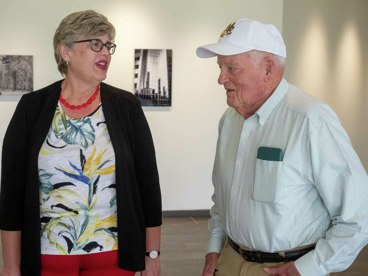 """Long time Midland College coach Delnor Poss talks with Rebecca Bell as he signs copies of his book, """"No Time Out! My Non-stop Life"""" 07/08/2021 at Midland College Allison Fine Arts Building. Tim Fischer/Reporter-Telegram"""