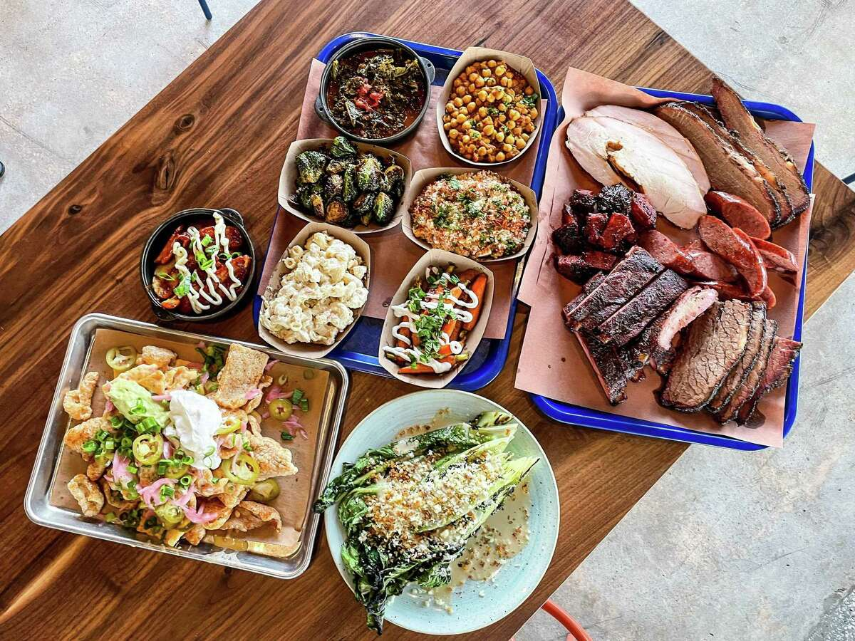From bottom left: Cracklin nachos, Money Cat Potatoes, a selection of sides, a selection of smoked meats, charred caesar salad atFeges BBQ Spring Branch