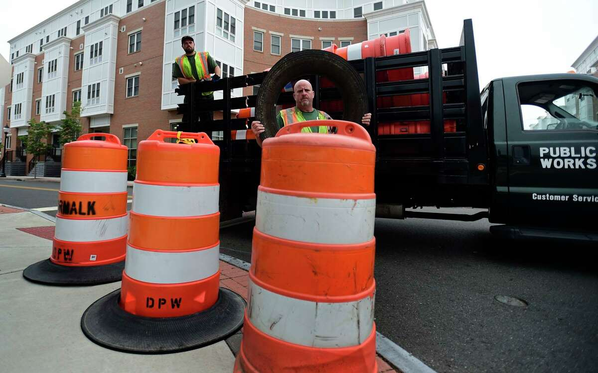 DPW workers Mike Delmonte and Doug Bamford place orange safety barrels along Water Street before the storm Thursday, June 8, 2021, in Norwalk, Conn.