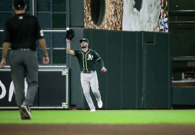 Oakland Athletics left fielder Seth Brown (15) catches the ball for an out against the Houston Astros during the fifth inning of an MLB game at Minute Maid Park on Thursday, July 8, 2021, in Houston. Photo: Godofredo A. Vásquez, Staff Photographer / © 2021 Houston Chronicle