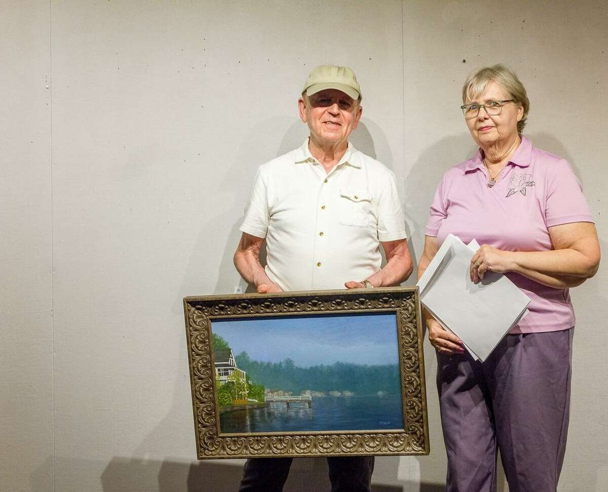 """George Voyajolu receiving the Award for Excellence from Sue Lapardo for his oil painting """"Early Morning Mist."""""""