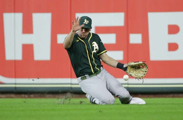 Oakland Athletics right fielder Stephen Piscotty (25) is unable to get catch a ball hit by Houston Astros right fielder Kyle Tucker (30) during the seventh inning of an MLB game at Minute Maid Park on Thursday, July 8, 2021, in Houston. Photo: Godofredo A. Vásquez, Staff Photographer / © 2021 Houston Chronicle
