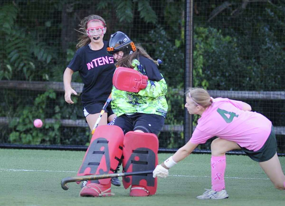 Greenwich High School field hockey goalie Martha Holland makes a stop as Greenwich Academy field hockey player Ashley Jones, #4, right, attempts to play to play the rebound during girls field hockey game between Greenwich High School and Greenwich Academy at Greenwich Academy, Tuesday afternoon, Sept. 14, 2010. GA won the game over GHS, 7-0.