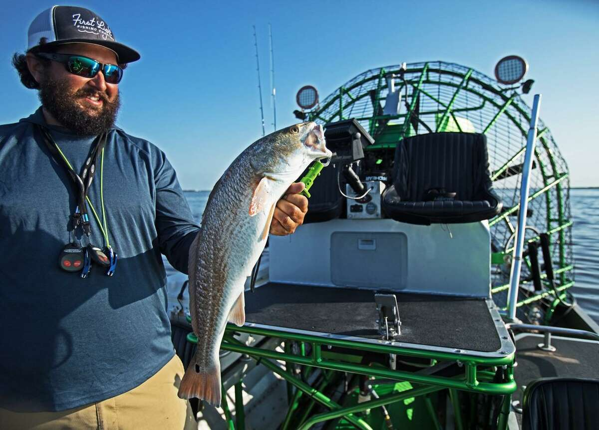 With the high seats and propeller of his airboat in the background, Capt. Jared McCulloch displays a 27-inch red in the early-morning sun on a skinny-water flat on the edge of South Bay where regular boats would run aground.