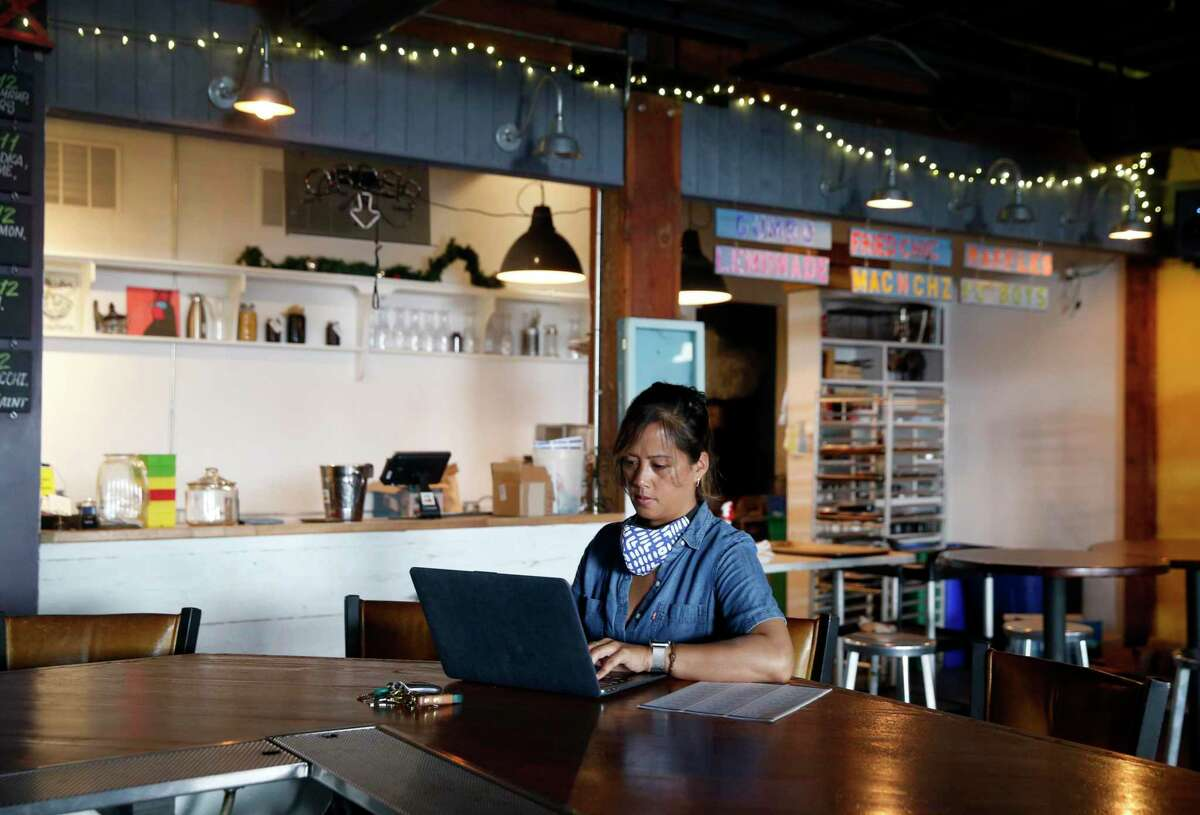 """Deanna Sison takes a break from preparing lunches to check the status of her federal small business loan application at her Little Skillet restaurant in San Francisco last year. """"Programs like the S.F. Small business Recovery Fund will continue to help us build a path to recovery,"""" she said Thursday."""