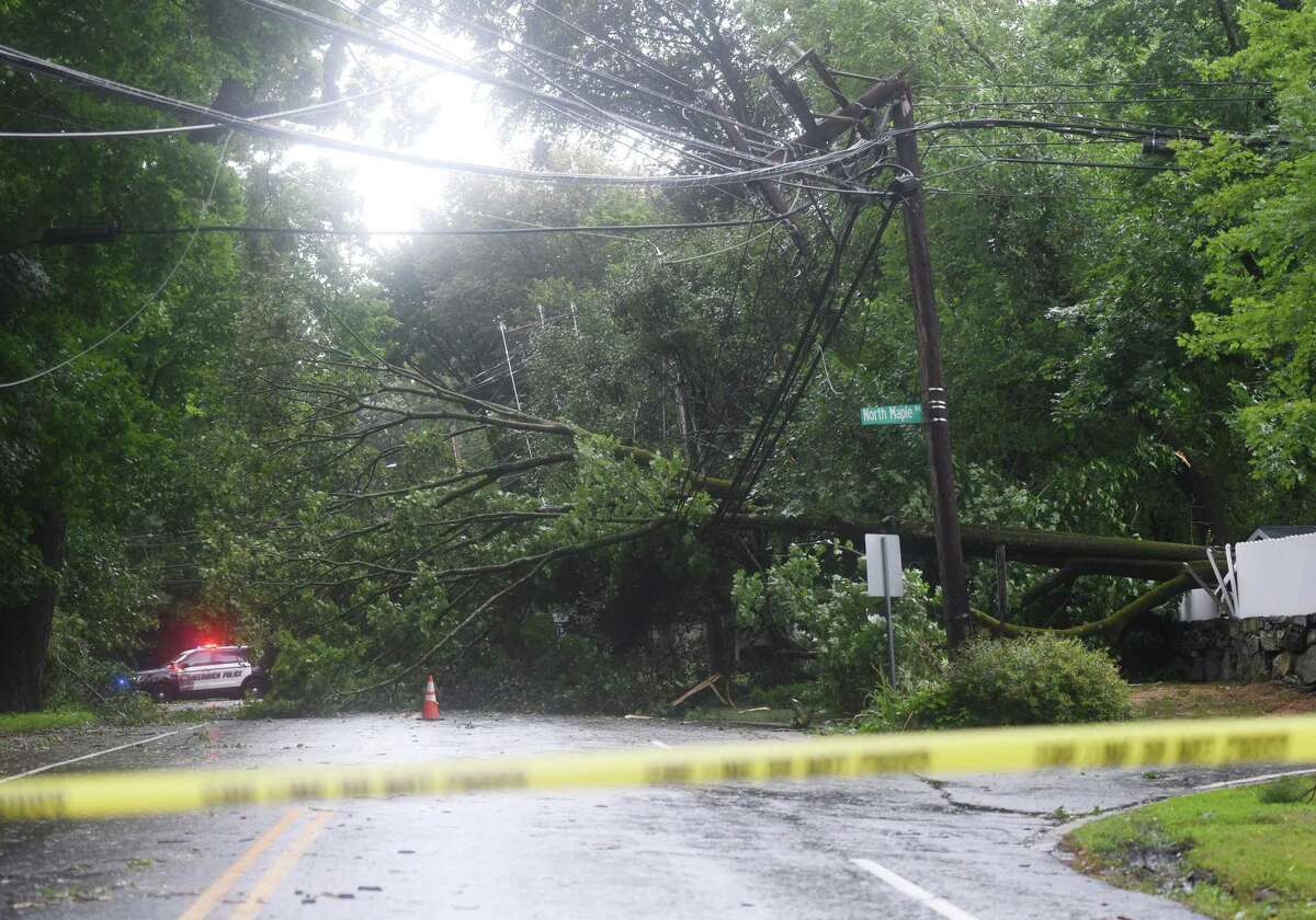 A tree takes down power lines on Lake Avenue at the intersection with North Maple Avenue from Tropical storm Isaias in Greenwich, Conn. Tuesday, Aug. 4, 2020. The first tropical storm of the 2021 season is expected to hit Friday.
