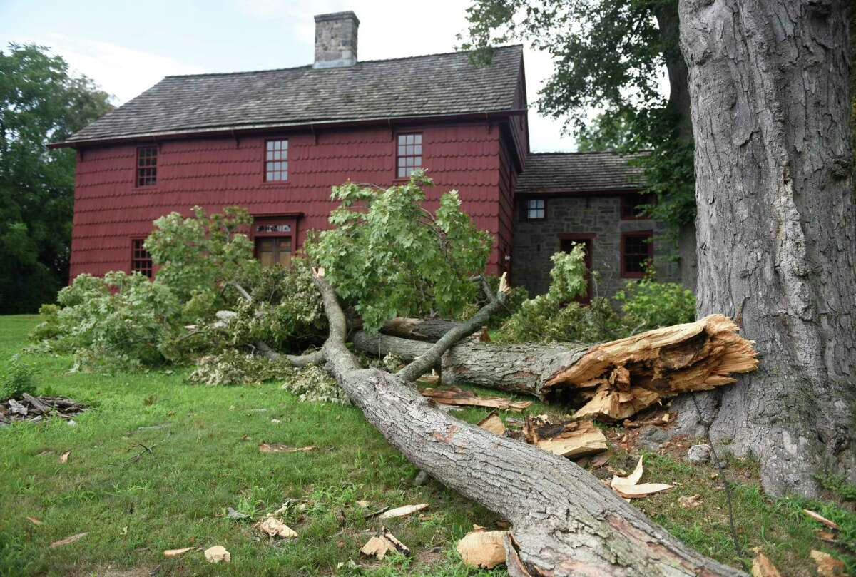 A downed tree just avoids causing damage to the historic Putnam Cottage, dated to c.1690, in Greenwich, Conn. Thursday, Aug. 6, 2020.