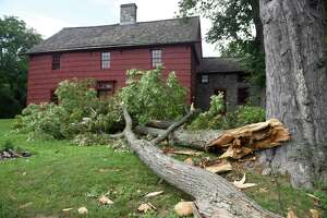 A downed tree just avoids causing damage to the historic Putnam Cottage, dated to c.1690, in Greenwich, Conn. Thursday, Aug. 6, 2020. The first tropical storm of the 2021 season is expected to hit Friday.