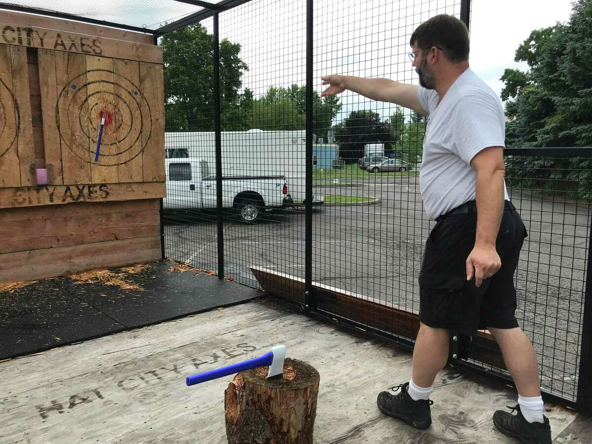Jason Clemence throws an ax on Thursday in one of the trailers he built. Clemence is an owner of Hat City Axes, a Danbury-based mobile ax-throwing company that brings the activity to various locations.